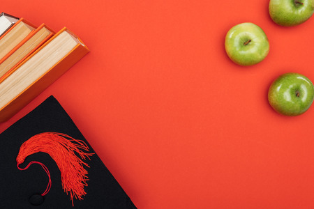 Top view of academic cap, books and apple on red surface 写真素材