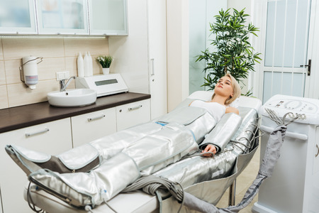 Blonde girl lying on beauty couch during pressotherapy session in clinic Foto de archivo