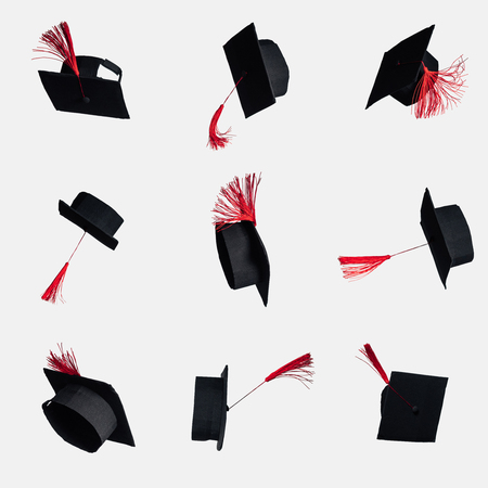 Black academic caps with red tassels isolated on white Imagens