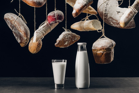milk in glass and bottle on table and bread with flour hanging on strings isolated on black