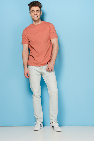 handsome and brunette man in t-shirt and jeans looking at camera Banque d'images