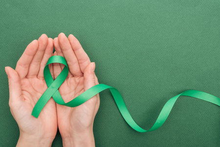 cropped view of woman holding green ribbon on green background with copy space