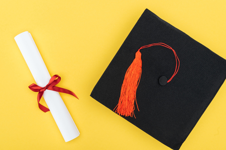 Top view of academic cap and diploma with red ribbon isolated on yellow Standard-Bild - 120485428