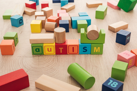 autism lettering made of multicolored cubes among building blocks on wooden surface