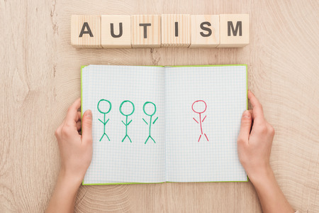 cropped view of woman holding opened notebook with drawn different humans near wooden cubes with autism lettering