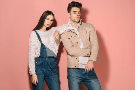 Morena y hermosa novia en overoles de mezclilla y novio guapo sobre fondo rosa