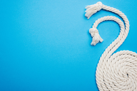 long white waved and twisted ropes with knots isolated on blue