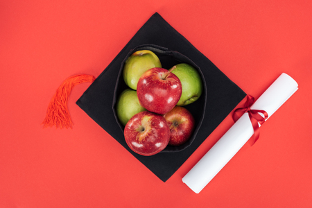 Top view of academic cap with apples and diploma on red surface 写真素材 - 120485983