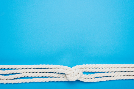 nautical white ropes with sailor knot isolated on blue Stock Photo