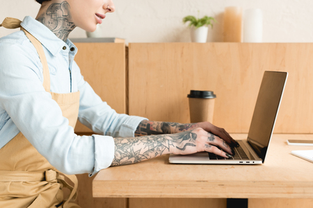 partial view of waitress using laptop while sitting at table near paper cup
