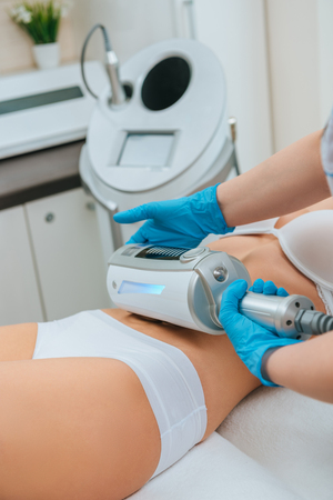 Cropped view of cosmetologist doing endospheres therapy for belly