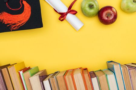 Top view of books, apples, academic cap and diploma on yellow surface