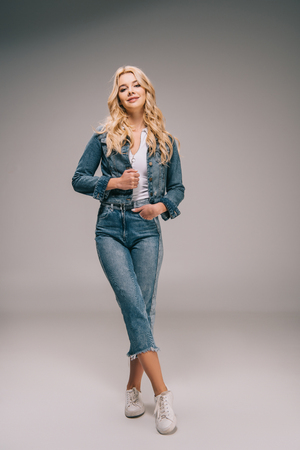 attractive blonde woman in denim jacket and jeans smiling and looking at camera