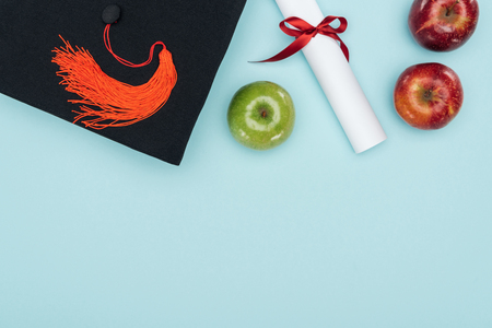Top view of academic cap, diploma and apples on blue surface