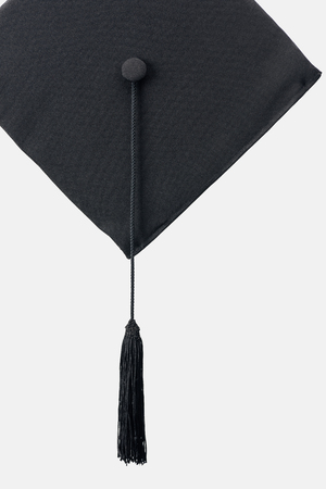 Black academic cap with long tassel isolated on white