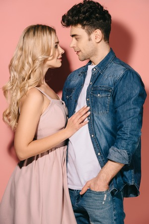 girlfriend in pink dress and handsome boyfriend in denim shirt hugging and looking at each other