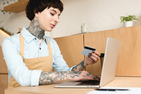 attractive waitress looking at credit card and writing in notebook