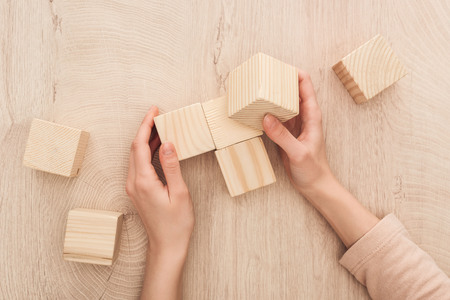 partial view of female hands near blank wooden cubes