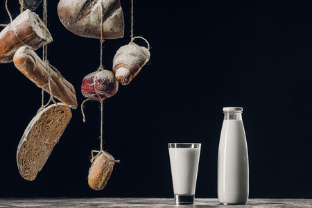 milk on table and bread with flour hanging on strings isolated on black with copy space