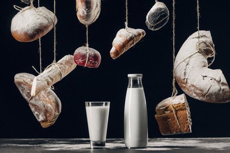 milk on table and bread with flour hanging on strings isolated on black