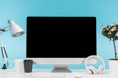 workplace with computer, lamp, cup, coffee to go, headphones and flowerpot on white table on blue background