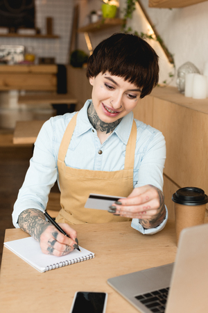 smiling waitress looking at credit card and writing in notebook Banque d'images - 120487505