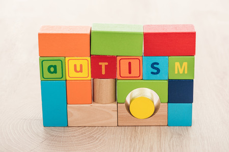 autism lettering made of colorful building blocks on wooden surface