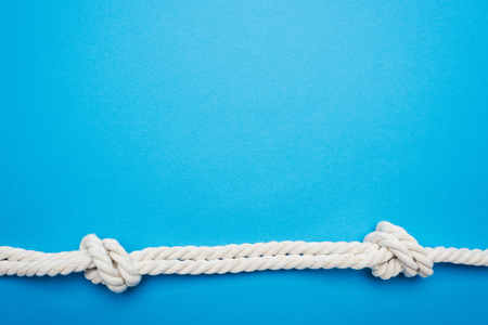 white long twisted ropes with sea knots isolated on blue Imagens