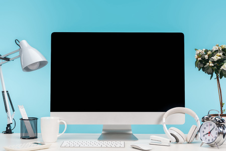workplace with computer, lamp, stationery and headphones on white table on blue background Stock Photo