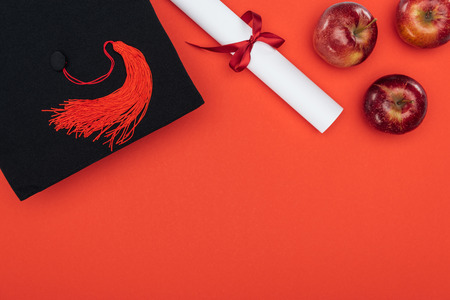 Top view of academic cap, diploma and apples on red surface
