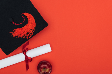 Top view of academic cap, diploma and apple on red surface