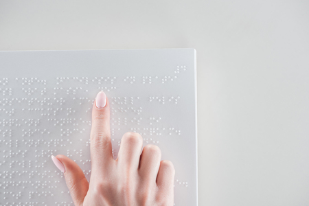 top view of young woman reading braille text on white paper with copy space