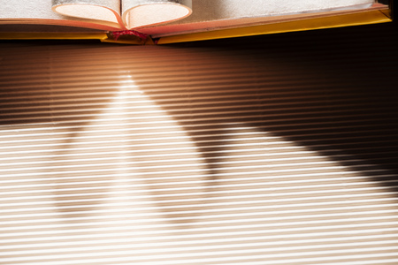 Open book with folded pages on textured surface with heart-shaped shadow
