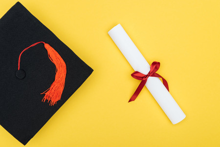 Top view of academic cap and diploma with red ribbon isolated on yellow
