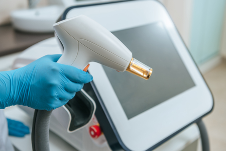 Cropped view of cosmetologist in rubber gloves holding laser device Stok Fotoğraf