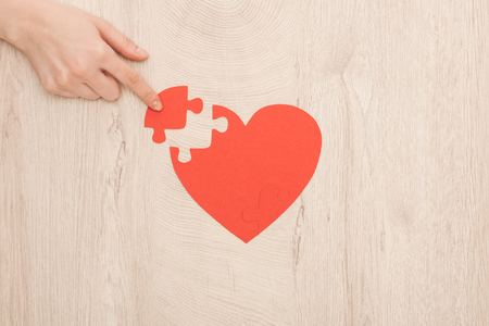 partial view of woman pointing with finger to puzzle of heart