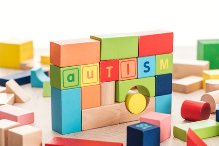autism lettering made of colorful building blocks on wooden surface isolated on white