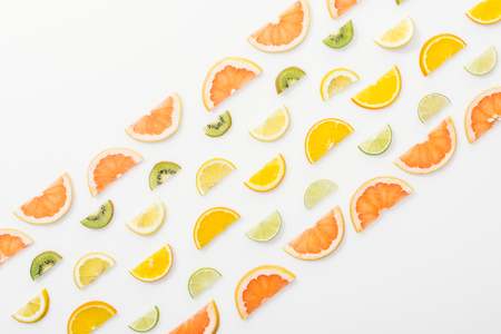 Flat lay with juicy cut fruits on white surface