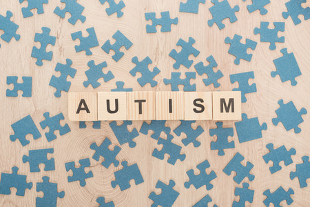 top view of autism lettering made of wooden blocks among blue puzzle pieces on wooden table