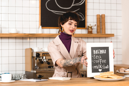smiling businesswoman placing menu board on bar counter in coffee shop Banque d'images - 120485374
