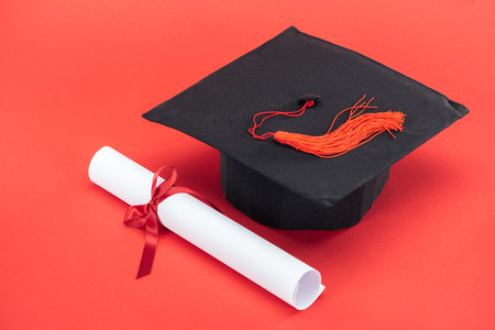 Academic cap with tassel and diploma with ribbon on red surface