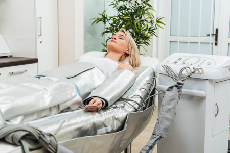 Blonde girl lying with closed eyes during pressotherapy session in clinic