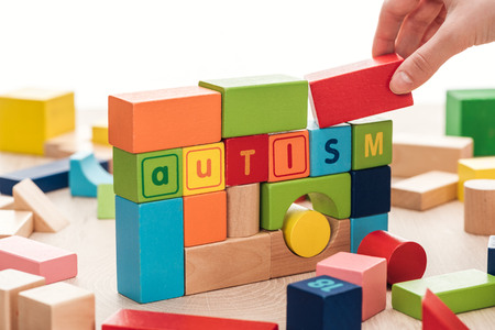 cropped view of female hand near autism lettering made of colorful building blocks on wooden surface isolated on white
