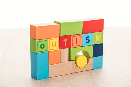 autism lettering made of multicolored building blocks on wooden surface isolated on white