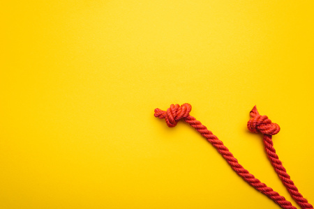 red and long ropes with twisted knots isolated on orange Stock fotó