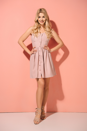 blonde and beautiful woman with hands on hips in pink dress smiling and looking at camera Stock Photo