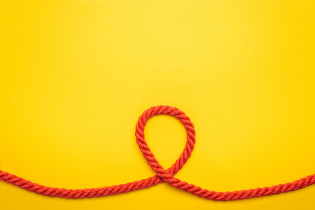 red long and curled rope isolated on orange