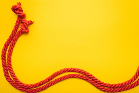 red waved ropes with knots isolated on orange
