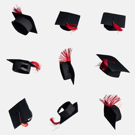 Black academic caps with red tassels isolated on white Stock Photo