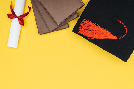 Top view of books, academic cap and diploma on yellow surface Standard-Bild - 120484978